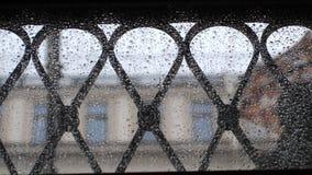 Widok od kropelek nadokiennych na zamazanych ludziach chodzi w zwolnionym tempie z parasolami podczas deszczu 1920x1080 zdjęcie wideo