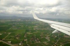 Widok od naddźwiękowego samolotu wieś z wiele górami przy daleko w chmurnym dniu i chałupami Fotografia Stock