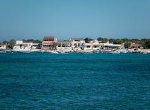 Widok od oceanu brzeg Algarve, Portugalia z łodziami i plażowymi domami na horyzoncie zdjęcia royalty free