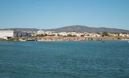 Widok od oceanu brzeg w Algarve, Portugalia w lecie z łodzią na plaży, domach i wzgórzach w tle, zdjęcia stock