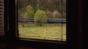 Widok od okno intymny dom: Europejczyka pociąg iść wzdłuż Pojedynczego kolejowego śladu wśród pięknej zielonej góry zbiory