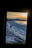 Widok od okno przy parą ludzie chodzi przy wybrzeżem Baikal Zdjęcie Stock