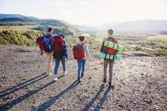 Widok od plecy cztery modnisia przyjaciela z podróż plecaka mienia rękami naprzód i bieg góra na zmierzchu obraz royalty free