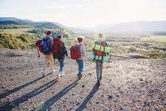 Widok od plecy cztery modnisia przyjaciela z podróż plecaka mienia rękami naprzód i bieg góra na zmierzchu obraz stock