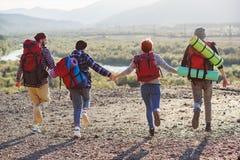 Widok od plecy cztery modnisia przyjaciela z podróż plecaka mienia rękami naprzód i bieg góra na zmierzchu obrazy royalty free
