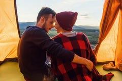 Widok od plecy młody człowiek i jego dziewczyny obsiadanie w namiocie, opiera przeciw siebie z ich nosami na zdjęcie stock