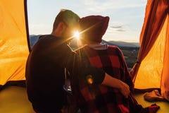 Widok od plecy m?ody cz?owiek i jego dziewczyny obsiadanie w namiocie, opiera przeciw siebie z ich nosami na zdjęcia stock