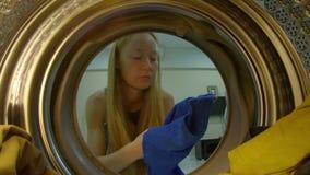 Widok od pralki jako m?oda kobieta stawia brudnego odziewa w je zbiory