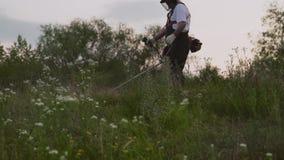 Widok od puszka męska ogrodniczka w trakcie tnącej trawy zbiory wideo
