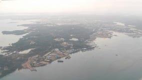 Widok od samolotowych okno seansu domów, budynków, chmur, gór, linia horyzontu, oceanu, statków i dużych łodzi, zdjęcie wideo