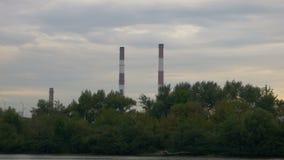 Widok od statku na wodzie na wielkich przemysłowych drymbach Fabryczni kominy przy zmierzchem kryzysu ekologiczny środowiskowy fo zdjęcie wideo