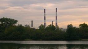 Widok od statku na wodzie na wielkich przemysłowych drymbach Fabryczni kominy przy zmierzchem Przerzuca most z przelotnymi samoch zbiory