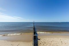 Widok piaskowata pla?a z groyne falochronem i spokojny morze pod majestatycznym niebieskim niebem zdjęcia royalty free