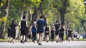 Widok plecy ludzie bieg i spacer przy pieszy ogródu parkiem Fotografia Stock