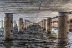 Widok pod mostem z drewnianymi kolumnami Zdjęcia Stock