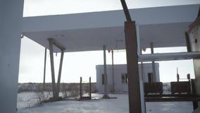 Widok porzucona benzynowa stacja obok drogi w zimie Zaniechana stacja benzynowa bez paliwa podpisuje zakrywać zbiory wideo