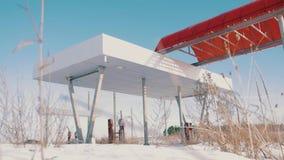Widok porzucona benzynowa stacja obok drogi w zimie Zaniechana stacja benzynowa bez paliwa podpisuje zakrywać zdjęcie wideo