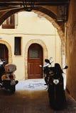 Widok przesmyk brukował ulicę i motocykle w tradycyjnym Greckim miasteczku Zdjęcia Royalty Free