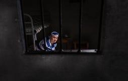 Widok przez żelaznego drzwi z więzienie barami na mężczyzna jest ubranym więzienie un Zdjęcia Royalty Free