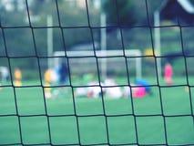 Widok przez futbolowej bramy zespalać się obsiadanie na murawy boisko do piłki nożnej Obrazy Stock