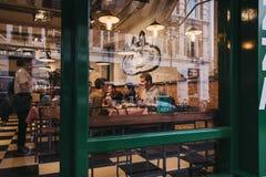 Widok przez okno ludzie wśrodku restauracji w Covent Garden, Londyn, UK fotografia royalty free