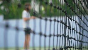 Widok przez zamazanej siatki przystojny mężczyzna bije tenisową piłkę z kantem zmiany ostrość siatka w zwolnionym tempie zbiory wideo