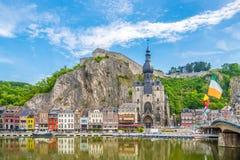 Widok przy bulwarem Meuse rzeka z domami i kościół Nasz damy wniebowzięcie w Dinant, Belgia - fotografia royalty free