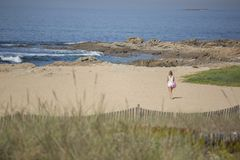Widok przy dziewczyną, samotnie i chodzący na plaży Leca da Palmeira, Portugalia obrazy stock