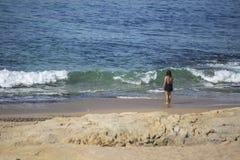 Widok przy dziewczyną z czerni suknią na plaży, samotny, statywowy i patrzejący morze, fotografia stock