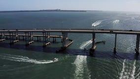 Widok przy mostem nad oceanem z ruchem drogowym na nim i łodziach wokoło zbiory wideo