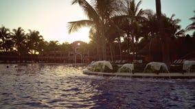 Widok przy pływackim basenem luksusowy hotel w kurorcie tropikalny wybrzeże przy zmierzchem Liście kokosowe palmy trzepocze w wia zbiory