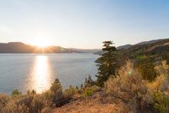 Widok pustynne trawy i bylica z położeniem za górami jeziora i słońca fotografia stock