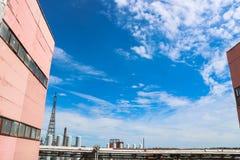 Widok rurociąg wiadukt z drymbami, kolumnami i budynkami, produkcja budynki, zbiorniki przeciw niebieskiemu niebu z chmurami zdjęcia royalty free