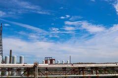 Widok rurociąg wiadukt z drymbami, kolumny zbiorniki przeciw niebieskiemu niebu z chmurami przy przemysłową chemiczną rafinerią fotografia royalty free