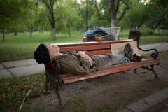 Widok starego człowieka lying on the beach na ławce w miasto parku obrazy stock