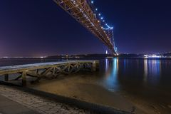 Widok stary molo w bankach Tagus Rzeczny Rio Tejo z 25 Kwietnia most na backgound przy nocą Fotografia Stock
