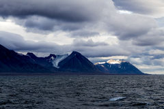 Widok Svalbard góry z słońca jaśnieniem od behing chmury Zdjęcia Royalty Free