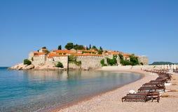 Widok Sveti Stefan wyspa na letnim dniu z plażą i loungers, Montenegro zdjęcie royalty free