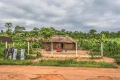 Widok tradycyjna wioska, dwa kobiety i dziecka obsiadanie przed pokrywającym strzechą domem z ścianami, dachu, terakoty i słomy obrazy royalty free