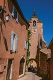 Widok tradycyjni kolorowi domy w ocher i zegarowy wierza w Roussillon, Zdjęcie Stock
