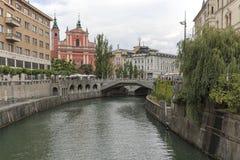 Widok Tromostovje most w Ljubljana i kilka turyści przechodzi obok Zdjęcie Stock