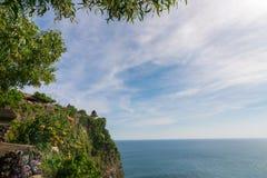 Widok Uluwatu faleza z pięknym jasnym niebem i błękitny morze w półdupkach Zdjęcia Royalty Free
