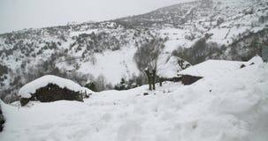 Widok wiejscy domy zakrywający śniegiem z górą w tle zbiory wideo