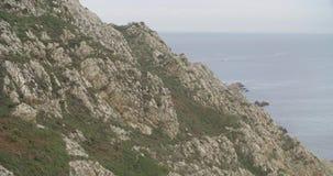 Widok wielka formacja skały blisko morza z łódkowatym żeglowaniem w horyzoncie zdjęcie wideo