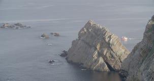 Widok wielka formacja skały blisko morza z łódkowatym żeglowaniem w prawej stronie zbiory