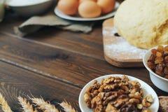 Widok wypiekowi składniki dla domowej roboty ciasta na ciemnym nieociosanym drewnianym tle Zdjęcia Stock