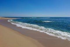Widok wzdłuż linii brzegowej pusta piaskowata plaża w Portugalia na pogodnym letnim dniu z niebieskim niebem, zdjęcie stock