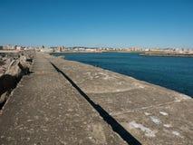 Widok wzdłuż schronienie ściany w Povoa De Varzim, Portugalia z morzem, schronieniem na dobrze i miastem w odległości obraz stock