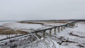 Widok z lotu ptaka ładunku pociąg przechodzi most dostarcza towary, paliwo, petrolium w zimie zbiory wideo
