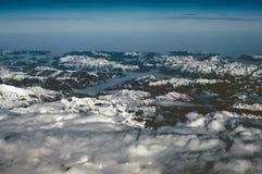 Widok z lotu ptaka śnieżne góry w zimie Latać przy zmierzchem nad chmury zdjęcia stock